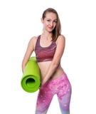 Счастливая sporty женщина при зеленая циновка смотря камеру в студии белизна изолированная предпосылкой Стоковое Фото