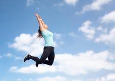 Счастливая sporty молодая женщина скача в голубое небо Стоковое фото RF