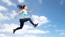 Счастливая sporty молодая женщина скача в голубое небо Стоковое Изображение RF