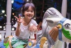 Счастливое азиатское катание девушки на лошади веселой идет круг Стоковое фото RF
