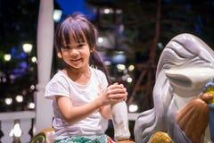 Счастливое азиатское катание девушки на лошади веселой идет круг Стоковое Фото
