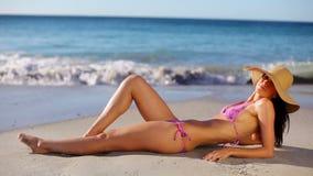 Счастливое брюнет лежа на песке акции видеоматериалы