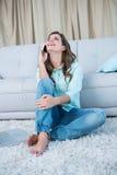 Счастливое брюнет на телефоне сидя на поле Стоковое Изображение