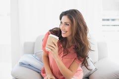 Счастливое брюнет сидя на ее софе держа устранимую чашку стоковое фото rf
