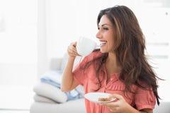 Счастливое брюнет сидя на ее софе держа чашку и поддонник с a стоковая фотография rf