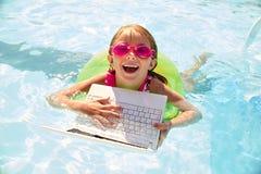 Счастливое заплывание девушки в бассейне с кольцом и компьтер-книжкой Стоковая Фотография