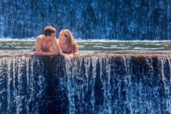 Счастливое заплывание пар в бассейне водопада природного источника стоковые изображения rf