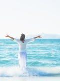 Счастливое ликование молодой женщины на береге моря. вид сзади стоковое фото