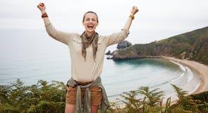 Счастливое ликование hiker женщины перед ландшафтом вида на океан стоковые изображения