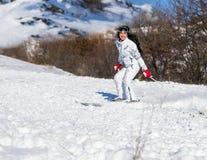 Счастливое катание на лыжах женщины на наклоне в яркий свет Стоковое Фото