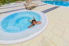 Счастливое красивое заплывание маленькой девочки и ослаблять в малом джакузи около бассейна Стоковые Фото