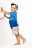 Счастливое маленькое белокурое усаживание мальчика, зеленое bacground Стоковое фото RF