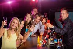 Счастливое молодые люди clinking с шампанским внутри Стоковые Фото