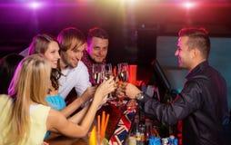 Счастливое молодые люди clinking с шампанским внутри Стоковая Фотография