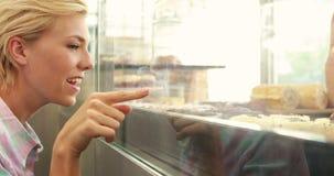 Счастливое довольно белокурое указывая пирожное видеоматериал