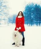 Счастливое предприниматель молодой женщины при белая собака Samoyed идя в зиму Стоковое Изображение