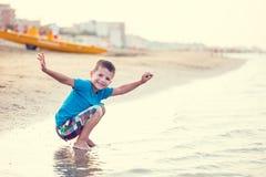Счастливое сидение на корточках мальчика на пляже Стоковая Фотография RF