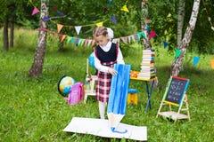 Счастливое сочинительство чертежа девушки ребенк ребенка школьницы с огромный большим Стоковая Фотография RF