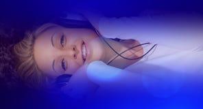 счастливое слушая нот к детенышам женщины Стоковая Фотография RF