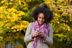 Счастливое текстовое сообщение чтения молодой женщины на мобильном телефоне