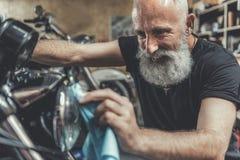 Счастливое усмехаясь мотоцилк чистки старика Стоковая Фотография RF