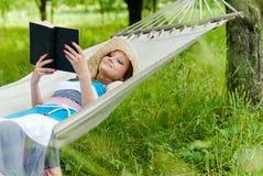 Счастливое чтение девушки в гамаке в зеленом парке outdoors Стоковое Изображение