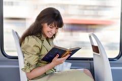 Счастливое чтение девушки в трамвае Стоковая Фотография