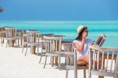 Счастливое чтение девушки на тропическом белом пляже Стоковые Изображения RF