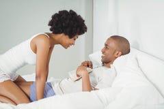 Счастливое чтение пар на кровати Стоковое Фото