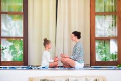 Счастливое annd девушки ее мать делая йогу работайте outdoors Стоковые Фото