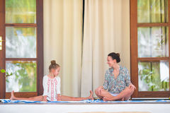 Счастливое annd девушки ее мать делая йогу работайте outdoors Стоковое фото RF