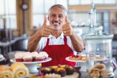 Счастливое barista смотря камеру и показывать большие пальцы руки вверх Стоковые Фотографии RF