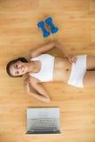 Счастливое sporty брюнет лежа рядом с компьтер-книжкой и гантелями стоковое изображение rf