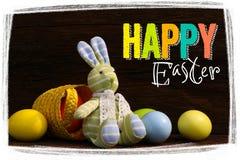 Счастливой яичка игрушки зайчика пасхи покрашенные корзиной Стоковое фото RF