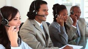 Счастливые агенты центра телефонного обслуживания нося шлемофоны видеоматериал