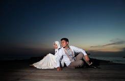 Счастливые азиатские мусульманские пары внешние на пристани Стоковая Фотография