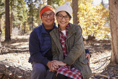 Счастливые азиатские пары сидя в лесе смотря к камере стоковое фото