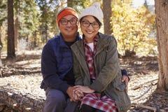 Счастливые азиатские пары сидя в лесе смотря к камере стоковые изображения rf