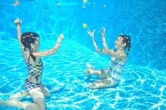 Счастливые активные дети плавают в бассейне и игре под водой Стоковое фото RF