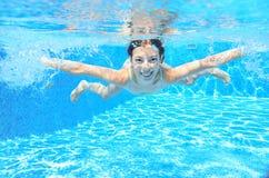 Счастливые активные подводные заплывы ребенка в бассейне Стоковая Фотография