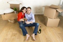 Счастливые американские пары сидя на поле распаковывая совместно праздновать при здравица шампанского двигая в новый дом Стоковые Фотографии RF