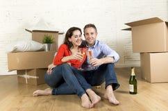 Счастливые американские пары сидя на поле распаковывая совместно праздновать при здравица шампанского двигая в новый дом Стоковые Изображения