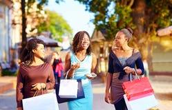 Счастливые африканские девушки идя улица с хозяйственными сумками Стоковое Фото