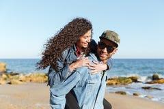 Счастливые африканские любящие пары идя outdoors на пляж Стоковое Фото
