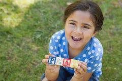 Счастливые алфавиты блока удерживания девушки как 'игра' на парке Стоковые Изображения