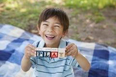 Счастливые алфавиты блока удерживания мальчика как 'игра' на парке Стоковое Изображение RF