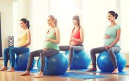 Счастливые беременные женщины работая на fitball в спортзале Стоковые Изображения