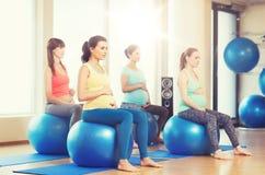 Счастливые беременные женщины работая на fitball в спортзале Стоковая Фотография RF