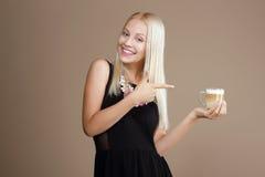 Счастливые белокурые пункты женщины вне к чашке кофе Стоковые Изображения