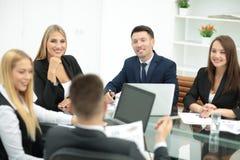 Счастливые бизнесмены говоря на встрече на офисе Стоковое Фото